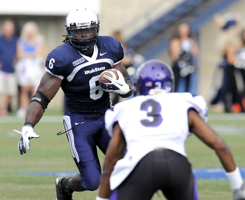 Utah State running back Robert Turbin (6) carries the ball downfield as Weber State cornerback Devin Pugh defends during their game, Saturday September 10, 2011, in Logan, Utah. (AP Photo/The Herald Journal, Eli Lucero)