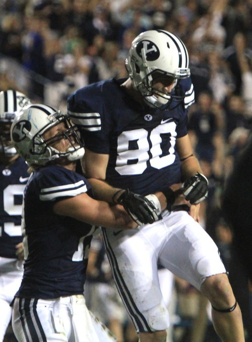 Rick Egan  | The Salt Lake Tribune   Brigham Young Cougars quarterback Riley Nelson (13)celebrates tight end Marcus Mathews (80) BYU defeated Utah State, 27-24 on this touchdown pass with 11 seconds left in the game,  in Provo, Friday, September 30, 2011.