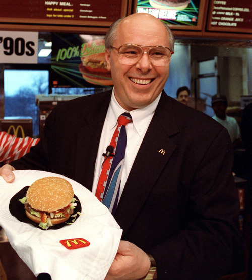 In this file photo of March 13, 1991, (then) McDonald's Corp. President Ed Rensi shows off the McLean Deluxe Burger during a news conference at the company's Oak Brook, Ill., headquarters. The lower fat hamburger made with seaweed derivative never really caught on with customers.  (AP Photo/Ralf-Finn Hestoft, File)