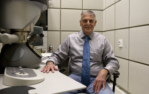 Israeli scientist Daniel Shechtman poses next to a transmission electron microscope at the Haifa Technion, Haifa, Israel, Wednesday, Oct. 5, 2011. Shechtman won the 2011 Nobel Prize in chemistry on Wednesday for his discovery of quasicrystals, a mosaic-like chemical structure that researchers previously thought was impossible. (AP Photo/Ariel Schalit)