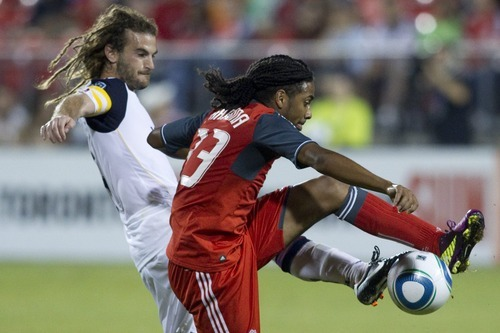 Toronto FC 's Javier Martina, right, tussles with Real Salt Lake's Kyle Beckerman during the second half of an MLS scocer game in Toronto, Saturday, Aug. 13, 2011. (AP Photo/The Canadian Press, Chris Young)