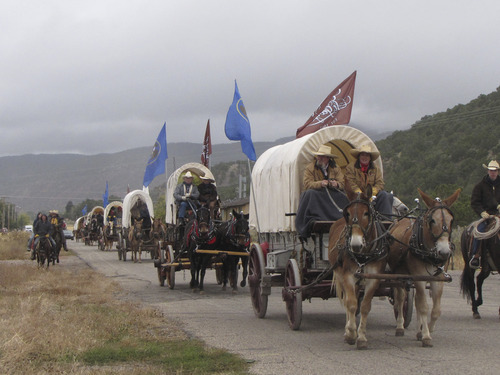 Mark Havnes  |  The Salt Lake Tribune A wagon train commemorating the 150th anniversary of the settlement of St. George rolls out of Parowan on Saturday at the start of an eight-day journey. The 30 wagons taking part are flying flags of Utah and St. George.