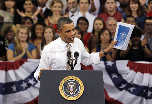 President Barack Obama holds up the American Jobs Act as he speaks Sept. 14, 2011, at North Carolina State University in Raleigh, N.C. In Obama's sales pitch for his jobs bill, there are two versions of reality: The one in his speeches and the one actually unfolding in Washington. (AP Photo/Gerry Broome)