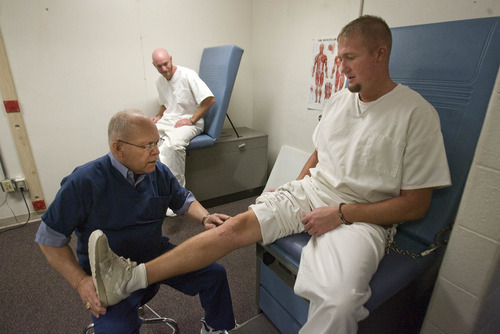 Paul Fraughton | The Salt Lake Tribune With one arm and a leg shackled, prisoner Mark Johnson is examined by physical therapist Bohn Bales at the Utah State Prison.   Wednesday, October 5, 2011