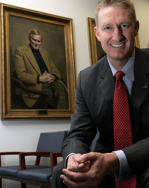 University of Utah Hinckley director Kirk Jowers with a portrait of the first Hinckley director J.D. Williams over his shoulder.
