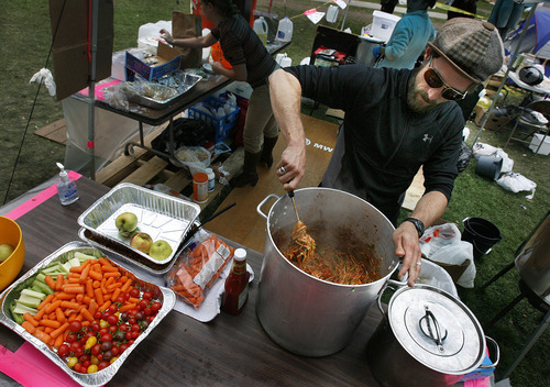 Scott Sommerdorf  |  The Salt Lake Tribune              Seth Neily stirs a batch of spaghetti as he and other volunteers make dinner for the Occupy SLC campers in their growing tent city in Pioneer Park, Monday, October 10, 2011.