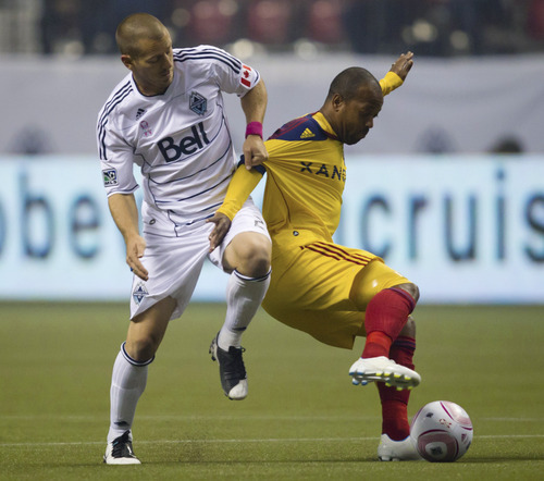 Vancouver Whitecaps' Jordan Harvey, left, ties up Real Salt Lake's Andy Williams during the first half of an MLS soccer game in Vancouver, British Columbia, on Thursday, Oct. 6, 2011. (AP Photo/The Canadian Press, Darryl Dyck)