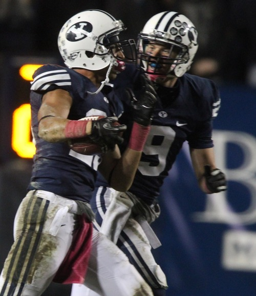 Rick Egan  | The Salt Lake Tribune   Brigham Young Cougars defensive back Travis Uale (23) celebrates with Daniel Sorensen (9)after intercepting a pass for BYU, in football action, BYU vs. San Jose State, at Lavell Edwards stadium, Saturday, October 8, 2011.