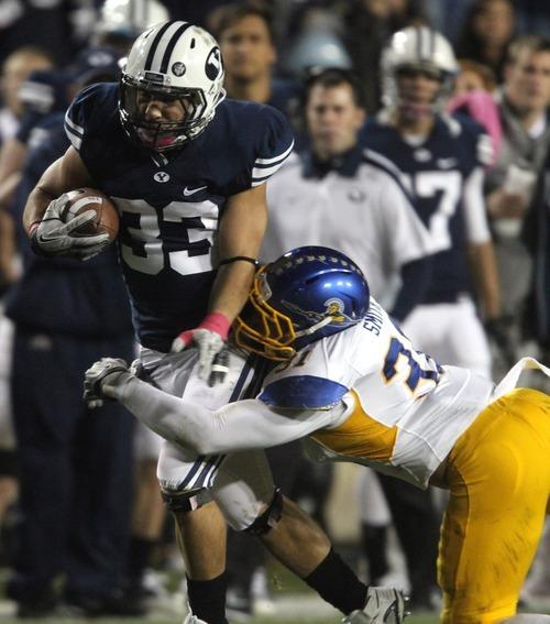 Rick Egan  | The Salt Lake Tribune   Brigham Young Cougars running back Bryan Kariya (33) gets past San Jose State Spartans linebacker Keith Smith (31) in football action, BYU vs. San Jose State, at Lavell Edwards stadium, Saturday, October 8, 2011.