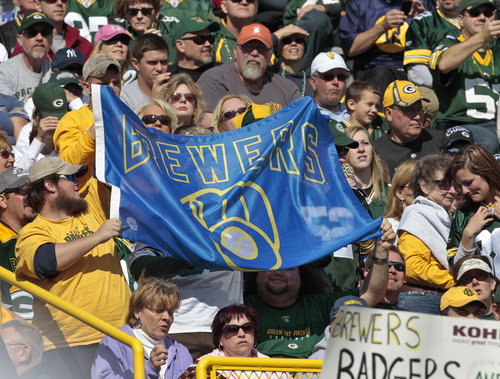 Green Bay Packers fans hold up a Milwaukee Brewers sign during the second half of the Packers' NFL football game against the St. Louis Rams on Sunday, Oct. 16, 2011, in Green Bay, Wis. The Brewers were scheduled to play the St. Louis Cardinals in Game 6 of the the NLCS on Sunday night in Milwaukee. (AP Photo/Mike Roemer)