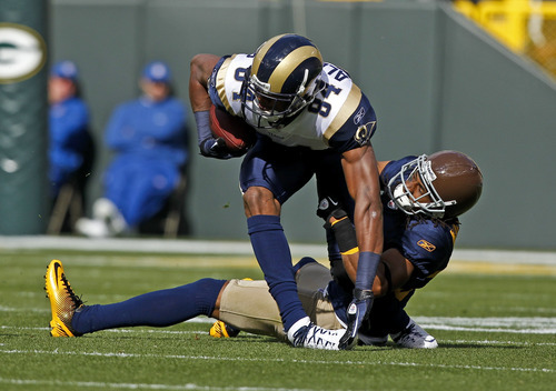 Green Bay Packers cornerback Tramon Williams, bottom right, tackles St. Louis Rams wide receiver Danario Alexander (84) during the first half of an NFL football game Sunday, Oct. 16, 2011, in Green Bay, Wis. (AP Photo/Jeffrey Phelps)