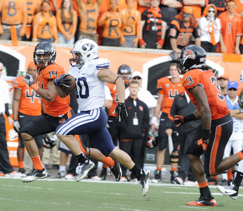 Oregon State's Jordan Poyer (14) and Anthony Watkins (3) chase BYU's JJ Di Luigi (10) during the second half of an NCAA college football game in Corvallis, Ore., Saturday Oct. 15, 2011. BYU won 38-28.(AP Photo/Greg Wahl-Stephens)