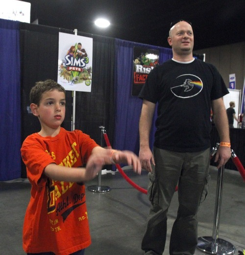 Rick Egan  | The Salt Lake Tribune  Tom Long and his 8-year-old son, Mason, play video games at the Geex Convention at the South Towne Expo Center on Saturday. A BYU study says profanity is a gateway to violence. The study looks at exposure to profanity from many sources, including games and other media.