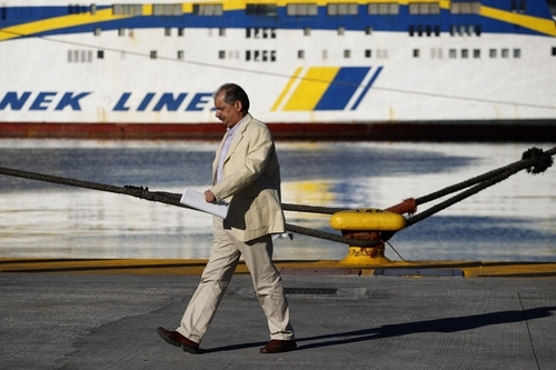 A man walks in front of  docked ships during a strike in the port of Piraeus, near Athens, on Wednesday, Oct. 19, 2011. A two-day general strike that unions vow will be the largest in years grounded flights, disrupted public transport and shut down everything from customs offices to shops and schools in debt-ridden Greece on Wednesday.(AP Photo/Petros Giannakouris)