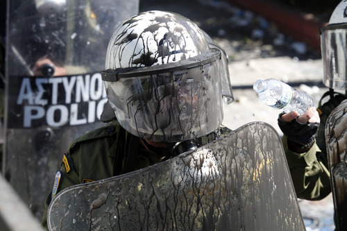 A riot police officer is covered by black paint during clashes outside the Greek Parliament, Wednesday Oct. 19, 2011. A two-day general strike that unions vow will be the largest in years grounded flights, disrupted public transport and shut down everything from shops to schools in Greece on Wednesday, as at least 50,000 protesters converged in central Athens. All sectors, from dentists, state hospital doctors and lawyers to shop owners, tax office workers, pharmacists, teachers and dock workers walked off the job ahead of a Parliamentary vote Thursday on new austerity measures. (AP Photo/Lefteris Pitarakis)