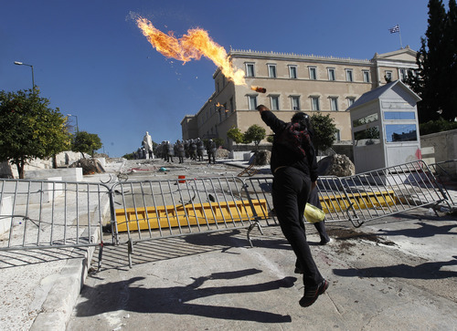 A protester throws a petrol bomb at riot police during clashes outside the Greek parliament in Athens, Wednesday, Oct. 19, 2011. Greek anger over new austerity measures and layoffs erupted into violence outside parliament on Wednesday, as demonstrators hurled chunks of marble and gasoline bombs and riot police responded with tear gas and stun grenades that echoed across Athens' main square. Wednesday was the first day of a two-day general strike that unions described as the largest protests in years, with at least 100,000 people marching through central Athens.  (AP Photo/Petros Giannakouris)