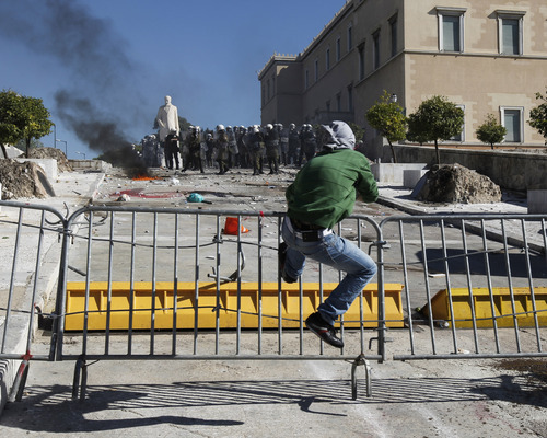 A protester kicks a police barrier during clashes outside the Greek parliament in Athens, Wednesday, Oct. 19, 2011. Greek anger over new austerity measures and layoffs erupted into violence outside parliament on Wednesday, as demonstrators hurled chunks of marble and gasoline bombs and riot police responded with tear gas and stun grenades that echoed across Athens' main square. Wednesday was the first day of a two-day general strike that unions described as the largest protests in years, with at least 100,000 people marching through central Athens.  (AP Photo/Petros Giannakouris)