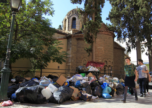 Tourists walk past a pile of rotting garbage outside a Greek Orthodox church in Athens on Tuesday, Oct. 18, 2011. Greek railway workers and journalists joined ferry crews, garbage collectors, tax officials and lawyers on Tuesday in a strike blitz against yet more austerity measures required if the country is to avoid defaulting on its debts.(AP Photo/Thanassis Stavrakis)