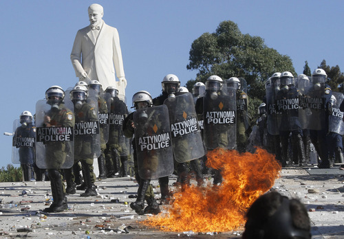 A petrol bomb explodes in front of riot policemen during clashes outside the Greek Parliament, Wednesday Oct. 19, 2011. A two-day general strike that unions vow will be the largest in years grounded flights, disrupted public transport and shut down everything from shops to schools in Greece on Wednesday, as at least 50,000 protesters converged in central Athens. All sectors, from dentists, state hospital doctors and lawyers to shop owners, tax office workers, pharmacists, teachers and dock workers walked off the job ahead of a Parliamentary vote Thursday on new austerity measures. (AP Photo)