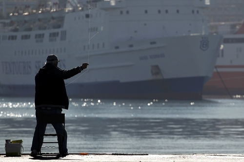 A man throws his fishing line in front of a  docked ship during a strike in the port of Piraeus, near Athens, on Wednesday, Oct. 19, 2011. A two-day general strike that unions vow will be the largest in years grounded flights, disrupted public transport and shut down everything from customs offices to shops and schools in debt-ridden Greece on Wednesday.(AP Photo/Petros Giannakouris)