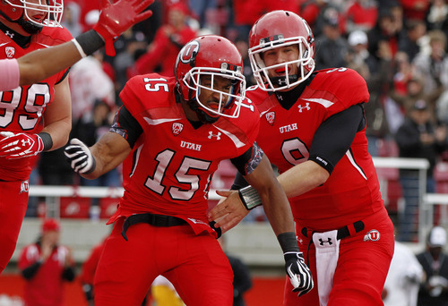Utah running back John White IV (15) celebrates his touchdown with quarterback Jon Hays (9) during the first half of an NCAA college football game, Saturday, Oct. 8, 2011, in Salt Lake City. (AP Photo/Jim Urquhart)