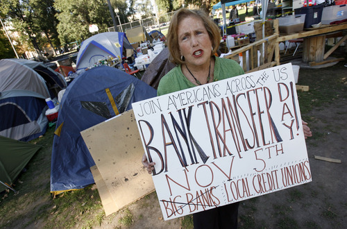 Francisco Kjolseth  |  The Salt Lake Tribune Elise Lazar of Salt Lake lends her voice in protesting big banks at the Occupy Salt Lake movement at Pioneer Park on Wednesday, October 19, 2011. Protesters have been accused of having no strategy to effect change, but that is changing with people like Elise who have decided to move their deposits from banks to more consumer-friendly and scandal-free institutions like credit unions.