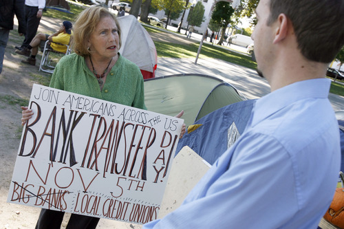 Francisco Kjolseth  |  The Salt Lake Tribune Elise Lazar of Salt Lake lends her voice in protesting big banks at the Occupy Salt Lake movement at Pioneer Park on Wednesday, October 19, 2011, as she talks with small business owner Devon Tew. Protesters have been accused of having no strategy to effect change, but that is changing with people like Elise who have decided to move their deposits from banks to more consumer-friendly and scandal-free institutions like credit unions. Devon Tew who used to work at Fidelity Investment supports the movement but disagrees with Lazar on the need for more regulation.