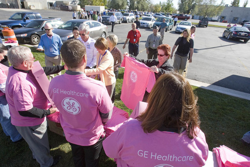 Paul Fraughton | The Salt Lake Tribune GE Healthcare employees  are given pink T shirts as they prepare to form a human cancer awareness ribbon in a field next to their Salt Lake City  facilities.   Wednesday, October 19, 2011