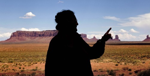 Matt York  |  The Associated Press Elsie Mae Begay, backdropped by Monument Valley, points to Oljato Mesa outside her Utah home in Monument Valley. Contaminated