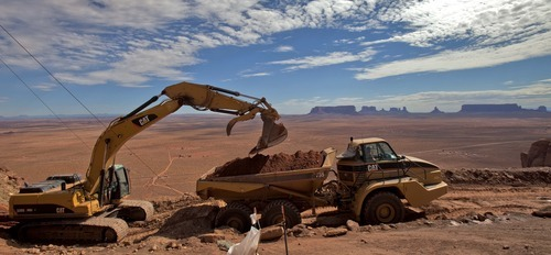 Matt York  |  The Associated Press Monument Valley looms in the background as contaminated soil is hauled to a repository down atop the Oljato Mesa Aug. 25 in Monument Valley, Utah. Tailings piles where uranium was mined decades ago are being removed by the U.S. Environmental Protection Agency. The $7.5 million project uses a cable system to transport some 20,000 cubic yards of material up the 800-foot Oljato Mesa where it came from.