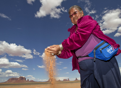 Matt York  |  The Associated Press Elsie Mae Begay, backdropped by Monument Valley, sifts sand near her home through her hands Aug. 24 in Monument Valley, Utah. Begay has led the Navajos' fight for awareness about uranium's dangerous legacy.