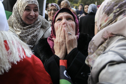 Liybans react to the death of Moammar Gadhafi outside the Libyan Embassy in London, Thursday, Oct. 20, 2011. (AP Photo/Sang Tan)