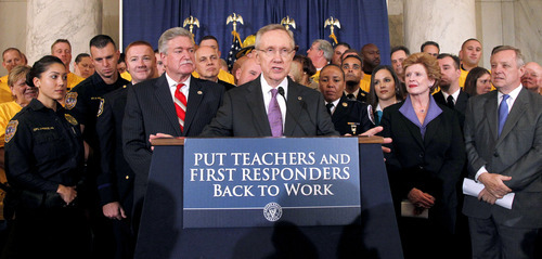 Senate Majority Leader Harry Reid of Nev. speaks during a news conference to urging the passage of the Teachers and First Responders Back to Work Act, Wednesday, Oct. 19, 2011, on Capitol Hill in Washington. He is joined by Senate Majority Whip Richard Durbin of Ill., right, Sen. Debbie Stabenow, D-Mich., second from right, and others.  (AP Photo/Haraz N. Ghanbari)