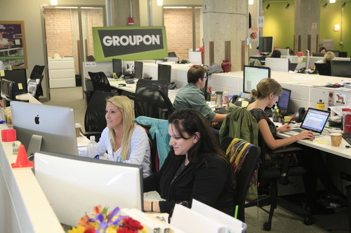 Rex Arbogast  |  The Associated Press Groupon employees Amanda Allegretti, left, and Becca Silvers work at the online coupon company's offices Thursday, Sept. 22, 2011, in Chicago.  Online coupon seller Groupon Inc. is discounting its expectations for its first stock offering, reported Friday.