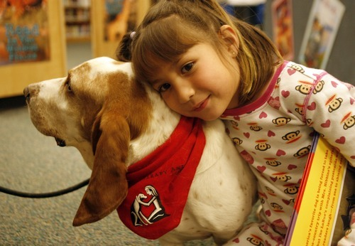 Rick Egan  | The Salt Lake Tribune   Copperview Elementary first grader Larissa Webb hugs Jack the dog, in the library, Wednesday, October 26, 2011.  Copperview Elementary students read with Intermountain Therapy Animals Reading Education Assistance Dogs in a program to improve their reading skills. Students also got to wear pajamas to school.