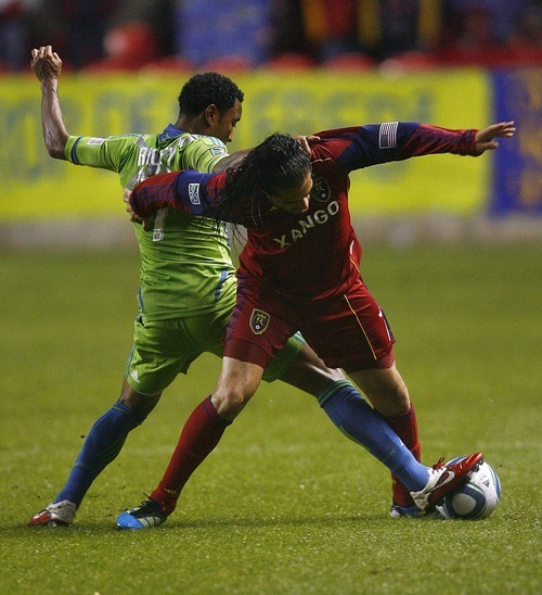Djamila Grossman     The Salt Lake Tribune  Real Salt Lake plays the Seattle Sounders at Rio Tinto Stadium in Sandy, Utah, on Saturday, May 28, 2011. Real's Fabian Espindola (7) and the Sounders' James Riley (7) fight over the ball.