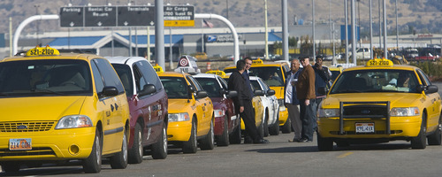 Al Hartmann  |  The Salt Lake Tribune Taxi drivers queue up for fares south of Salt Lake City International Airport on Thursday. Two local cab companies were passed over for contracting for on-demand services to two out-of-state firms.