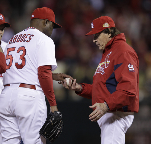 St. Louis Cardinals' Tony La Russa takes the ball from relief pitcher Arthur Rhodes (53) during the seventh inning of Game 7 of baseball's World Series against the Texas Rangers Friday, Oct. 28, 2011, in St. Louis. (AP Photo/Matt Slocum)