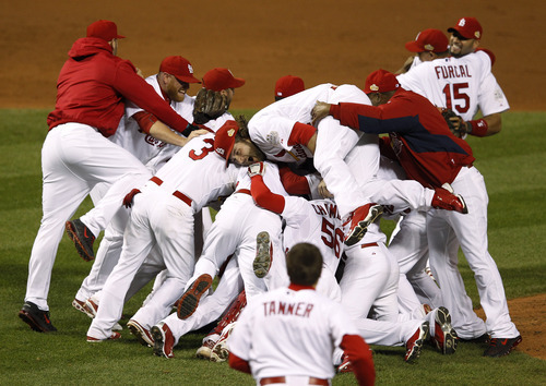 The St. Louis Cardinals celebrate after Texas Rangers' David Murphy hit a fly out to end Game 7 of baseball's World Series Friday, Oct. 28, 2011, in St. Louis. The Cardinals won 6-2 to win the series. (AP Photo/Eric Gay)