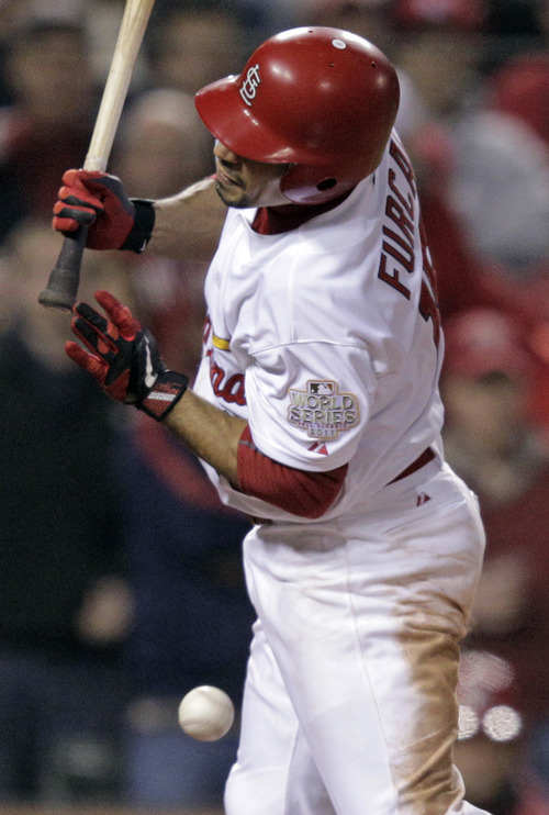St. Louis Cardinals' Rafael Furcal is hit by a pitch with bases loaded during the fifth inning of Game 7 of baseball's World Series against the Texas Rangers Friday, Oct. 28, 2011, in St. Louis. (AP Photo/Charlie Riedel)