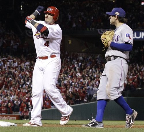 St. Louis Cardinals' Yadier Molina reacts in front of Texas Rangers' Ian Kinsler after hitting an RBI single during the seventh inning of Game 7 of baseball's World Series Friday, Oct. 28, 2011, in St. Louis. (AP Photo/Charlie Riedel)