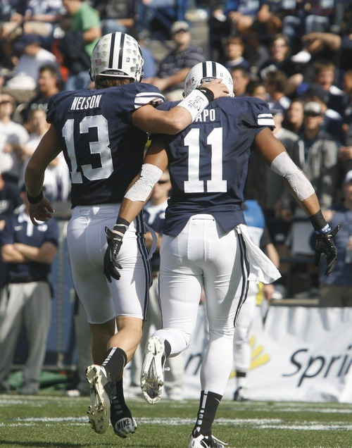 Rick Egan    The Salt Lake Tribune   Brigham Young Cougars quarterback Riley Nelson (13) walks off the field with   Ross Apo (11) after he scored a touchdown, in football action, BYU vs. Idaho State University football game, at Lavell Edwards Stadium, Saturday, October 22, 2011.