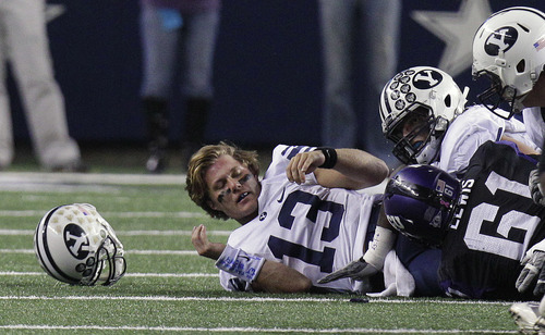 BYU quarterback Riley Nelson (13) looses his helmet on the sack by TCU defensive tackle Jon Lewis (61) during the first half of an NCAA college football game, in Arlington, Texas, on Friday, Oct. 28, 2011. (AP Photo/LM Otero)