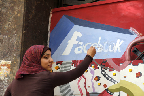 FILE - In this March 30, 2011, file photo. an art student from the University of Helwan paints the Facebook logo on a mural commemorating the revolution that overthrew Hosni Mubarak in the Zamalek neighborhood of Cairo, Egypt. The team from the CIA's Open Source Center, housed in a unassuming brick building in a Virginia industrial park, pores daily over tweets, Facebook, newspapers, TV news channels, local radio stations, Internet chat rooms _ anything overseas that anyone can access, and contribute to, openly. The center saw the uprising in Egypt coming said the center's director, Doug Naquin. The center already had