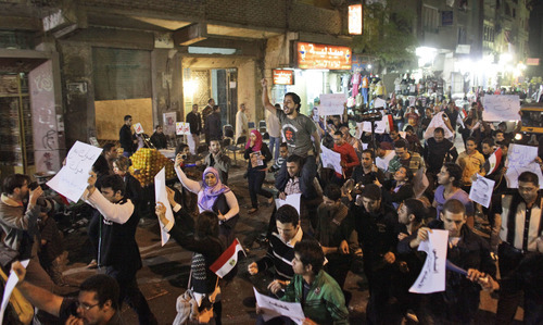FILE - In this Nov. 26, 2010, file photo, activists shout anti-government slogans as they march through the low-income neighborhood of Imbaba, in Cairo, Egypt. Egyptian activists organized several small