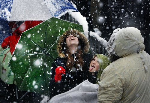 Scott Sommerdorf | The Salt Lake Tribune Samantha Marie, left, and Ally Burch from Layton try to catch snowflakes on their tongues Saturday as they wait in line at The Rail Event Center for free tickets to a Nov. 11
