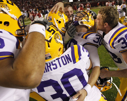 LSU kicker Drew Alleman (30) is embraced by teammates after the second half of an NCAA college football game against Alabama, Saturday, Nov. 5, 2011, in Tuscaloosa, Ala. Alleman kicked the winning field goal. LSU won 9-6. (AP Photo/Dave Martin)