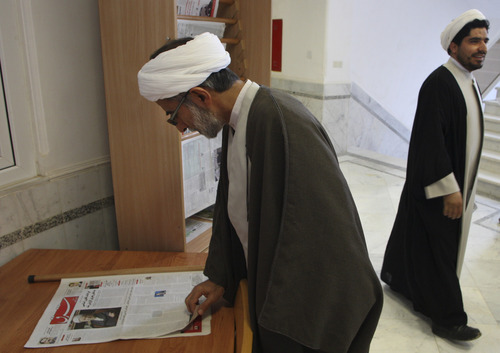 An Iranian cleric reads the pro-reform daily Shargh, or East newspaper, at the University of Religions and Denominations, in the city of Qom, 78 miles (125 kilometers), south of the capital Tehran, Iran, Wednesday, Nov. 9, 2011. (AP Photo/Vahid Salemi)