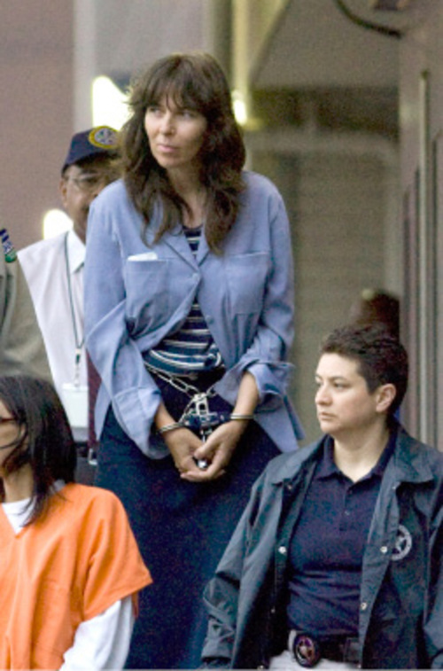 Jacqueline LeBaron, center, who is accused in the shooting deaths of three former sect members and the 8-year-old daughter of one of the adults in Houston and Irving, Texas, is taken to a transport van after appearing before a federal magistrate at the Bob Casey Federal Courthouse in Houston. (AP Photo/Steve Campbell)