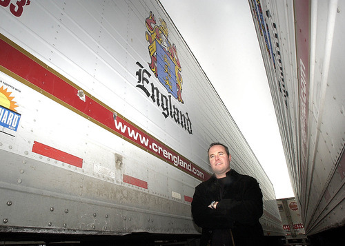 Paul Fraughton  |  Tribune file photo Sean Snow, a vice president of C.R. England Trucking, stands between two refrigerated trailers at the company's lot in 2004. Dan England, chairman of C.R. England Inc., has been elected chairman of the American Trucking Associations for a one-year term.